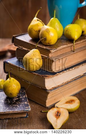some raw ripe small yellow pears on old book in studio