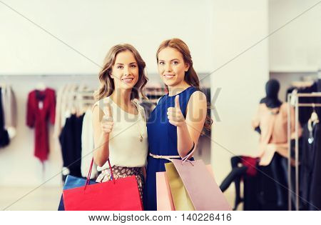 sale, consumerism and people concept - happy young women with shopping bags at clothing shop showing thumbs up