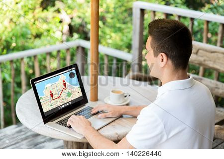 business, location, navigation, people and technology concept - close up of businessman typing on laptop computer with gps navigator map on screen outdoors on summer terrace and drinking coffee