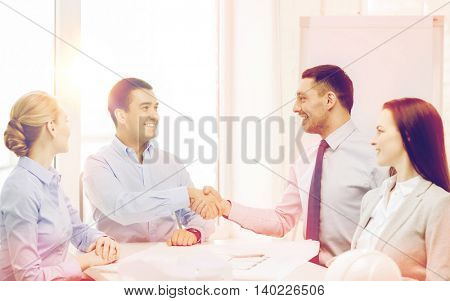 business, architecture and office concept - happy team of architects and designers in office shaking hands