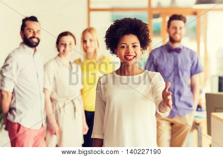 business, startup, people, gesture and teamwork concept - happy young african woman greeting by handshake over international creative team in office