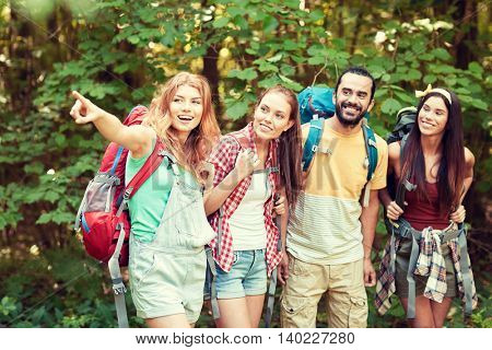adventure, travel, tourism, hike and people concept - group of smiling friends with backpacks pointing finger in woods
