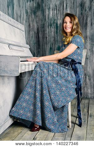 Romantic young woman playing the piano. Music and art concept.