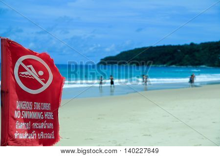 The red flag prohibiting swimming. A sea shore. Of the island.
