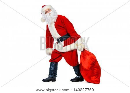 Funny Santa Claus with an effort pulls sack with gifts. Christmas celebration. Isolated over white.