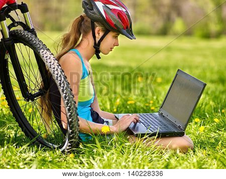 Girl with bicycle . Girl rides bicycle. Girl in bicycling sitting near bicycle and watch laptop. Cycling is good for health. Cyclist looking for open laptop. Summer outdoor.