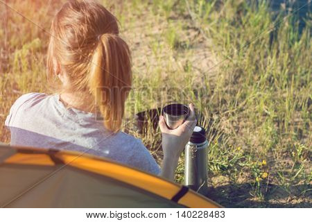 Girl hiker in a tent and holding a cup of warm tea. Mountains and lake in the background. Light leaks style. Girl on vacation enjoying the beauty of nature. Camping hiking lifestyle.