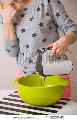 Young woman in long sleeve shirt with stars mixing and tasting dough for homemade muffins. Cooking and baking at home. Bright kitchenware and white mixer. Indoors.