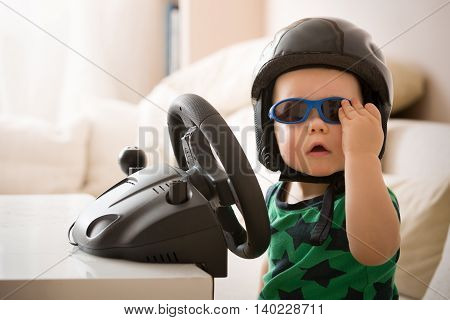 poster of Cute little kid boy in a helmet playing with Computer steering wheel. Future driver. Getting ready for professional driving. Child driving a car. Funny toddler boy indoors. Boy and a car.