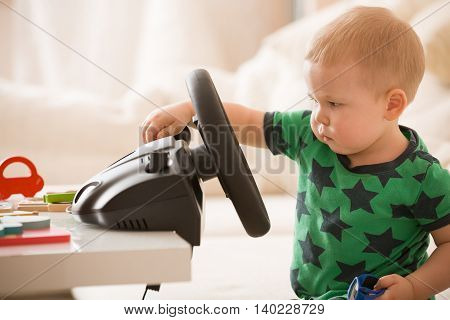 Cute little toddler boy playing with Computer steering wheel. Future driver. Getting ready for professional driving. Child driving a car. Funny toddler boy indoors. Boy and a car.