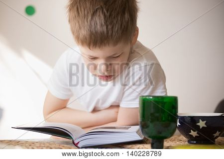 Cute kid boy reading a book while having his meal. Breakfast with reading.Child sitting at the table studying and drinking and eating. Learning.