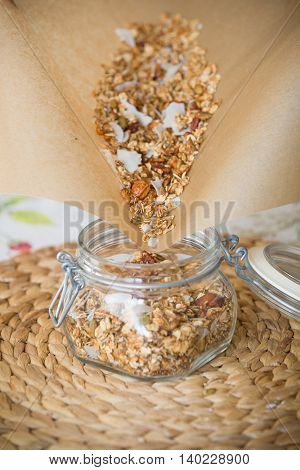 Homemade oat granola pouring into the glass jar. Straw table mat and baking paper as a background. Healthy snacks for energy. Diet and nutrition. Breakfast cereal.