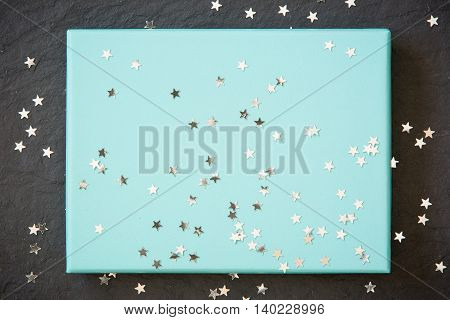 rectangular light blue box on black background with silver stars decorations. Holiday greetings. Engagement. turquoise on black board.