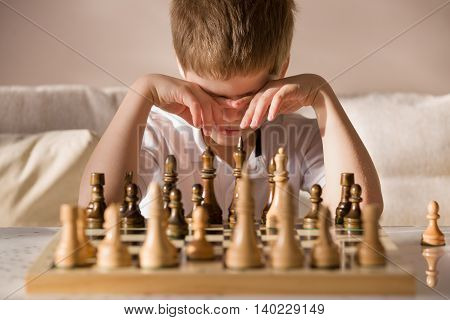 Boy playing chess in the room. Little clever boy concentrated and thinking while playing chess at home.