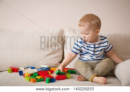 Cute little toddler boy in a striped shirt playing colorful plastic blocks on the sofa indoors. child having fun and building out of bright constructor bricks. Early learning. Creative.