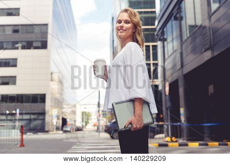 Beautiful young businesswoman with coffee cup holding notebook in her hands and looking at camera on city background. Split toned photo