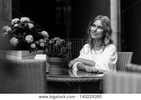 Beautiful romantic woman sitting alone in a cafe. Black and white image