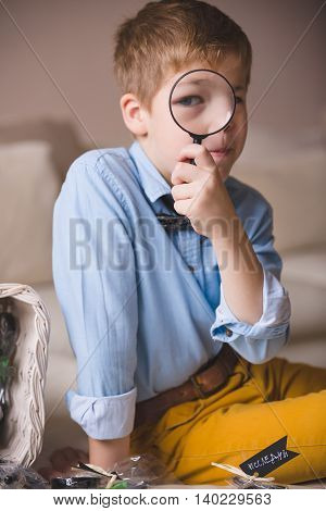 Portrait of cute schoolboy kid in blue shirt sitting on the sofa and looking through a magnifier. Child watching through magnifying glass. Indoors.