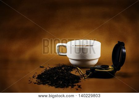 White Tea cup and dry leave tea on brown background.Background for office or business idea.target business or business vision or business plan.Background for tea business