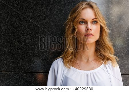 Close-up portrait of beautiful young girl with grey eyes and blond wavy hair