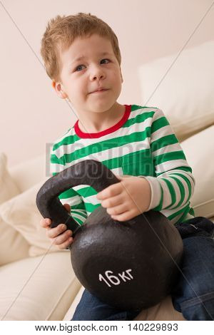 A cute boy in a striped t-shirt holding a huge weight. Young sportsman ready for competition. Sport with children. Healthy lifestyle