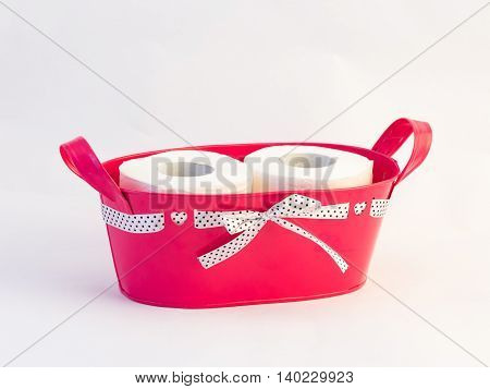 Pink basket tied with a ribbon with two rolls of toilet paper on a white background
