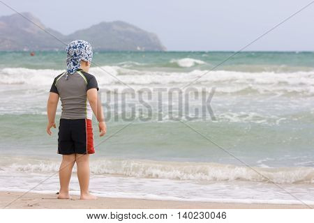 2 years old baby boy in a swimming suit on the sand beach. Ready to swim. Looking at the waves.
