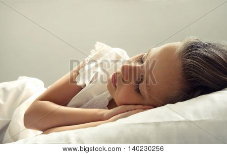 little girl is sleeping on white bad close up