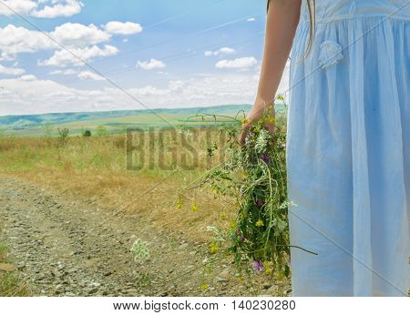 a young girl is holding wreath of wildflowers on wild road in the sunny day