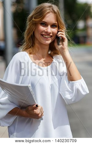 Portrait on street background of blond girl talking on cell phone