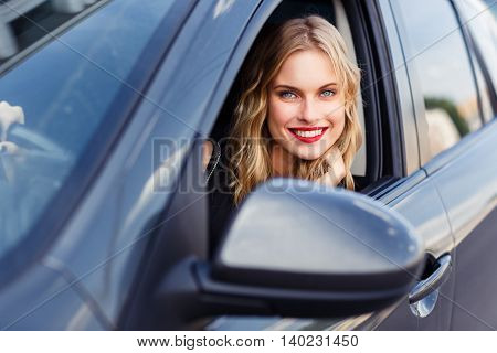 Portrait of young beautiful smiling girl in the car on summer day