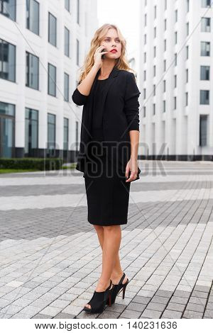 Portrait of elegant business lady in high heels in full-length talking on phone outdoors
