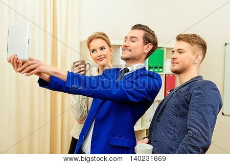 Three fellow employees are doing selfie in the office.