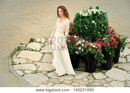 Beautiful young woman in luxurious white dress on a city street. Charming bride lady posing outdoor. Street fashion.