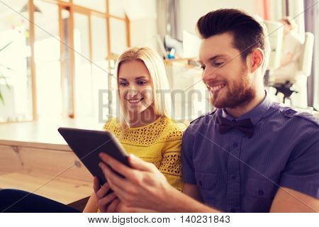 business, startup and people concept - happy creative team with tablet pc computer in office