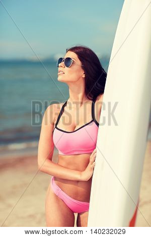 summer vacation, travel, surfing, water sport and people concept - young woman in swimsuit with surfboard on beach