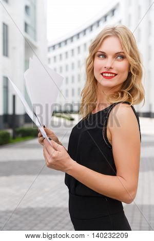 Young curly-headed blond woman with documents smiling on background of new white city buildings