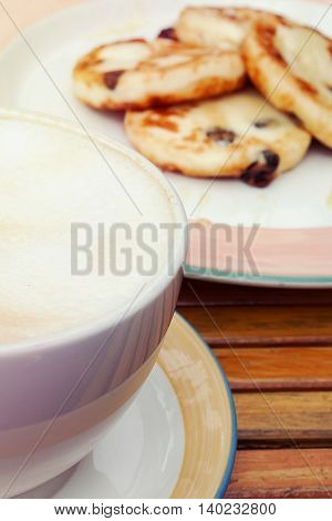 Large cup of cappuccino and freshly baked cottage cheese pancakes with raisin