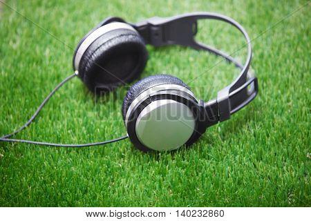 Headphones in a green grass. Horizontal photo