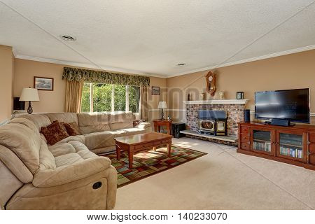 Living Room In Creamy Tones With Corner Sofa And Brick Fireplace.
