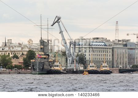 St. Petersburg, Russia - 16 July, River tugboats and the crane near the cruiser