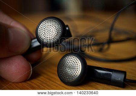 Male hand holding a silver and black perforated headphones (ear-buds) with cables