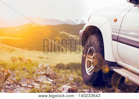 the wheel of an SUV on a cliff in the mountain