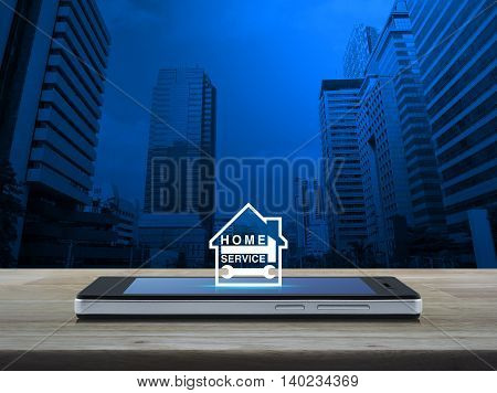 Hammer and wrench with house icon on modern smart phone screen on wooden table over city tower background Home service concept