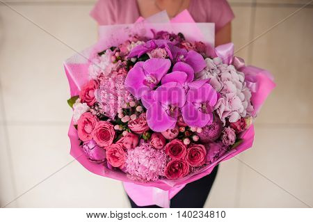 woman holding bright pink bouquet no face
