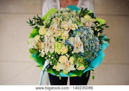 Woman holds a green bouquet no face