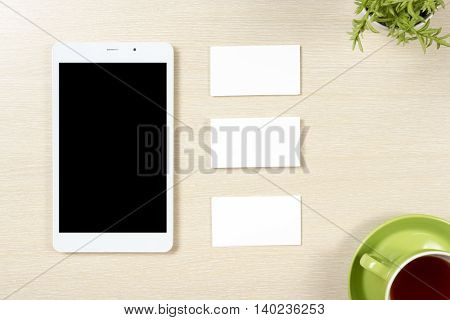 Business card blank, smartphone or tablet pc, flower and coffee cup at office desk table top view. Corporate stationery branding mock-up.