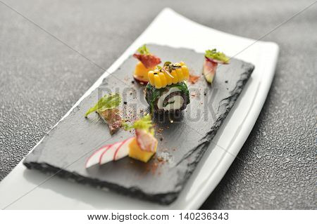 Rolls of meat and corn with herbs on black rock plate in restaurant
