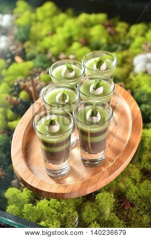 Glasses of pudding on wooden tray on green background