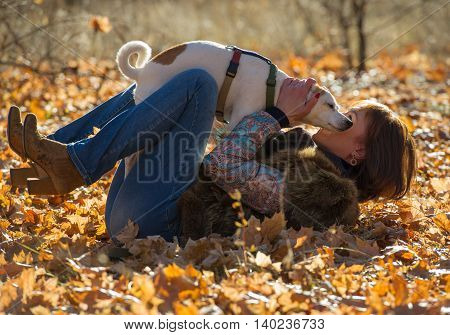 woman playing with the dog in the autumn park